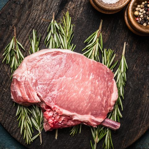 raw pork chop on rosemary and cutting board, dark rustic background