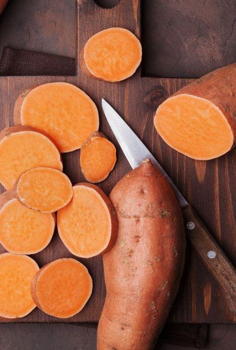 Rawsweet potatoes on wooden kitchen board top view. Organic food.