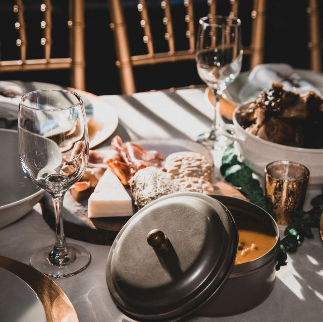 rays of sunlight on dinner table set up empty glasses and napkin wrapped flatware on dinner plates metal tin container of beans habichuelas out of focus chicken and appetizers partial view of chairs in the upper section of photo