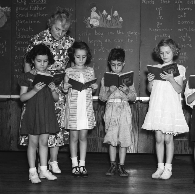 1930s line up of 5 elementary school students in front of blackboard reading books with teacher looking on  photo by h armstrong robertsclassicstockgetty images