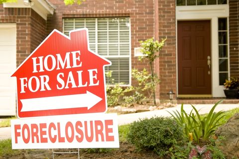 Real Estate Sign in yard of foreclosure house. For sale.