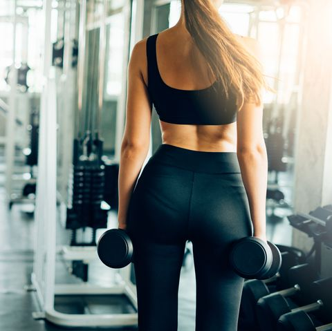 Rear View Midsection Of Woman With Dumbbells Standing In Gym