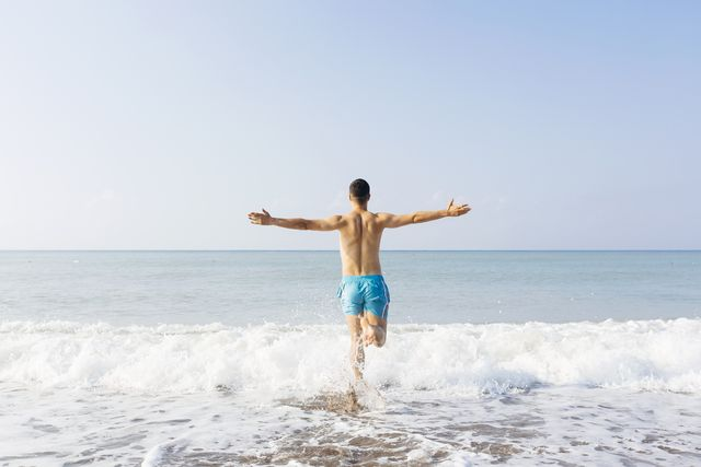 rear view of a young happy man with arms outstretched running towards the sea on a sunny day