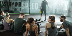 Rear view of athletic friends talking while having training class in a gym.