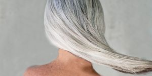 Rear view of bare shouldered mature woman with long grey hair