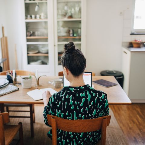 Rear view of businesswoman sitting on chair while using laptop at desk in home office