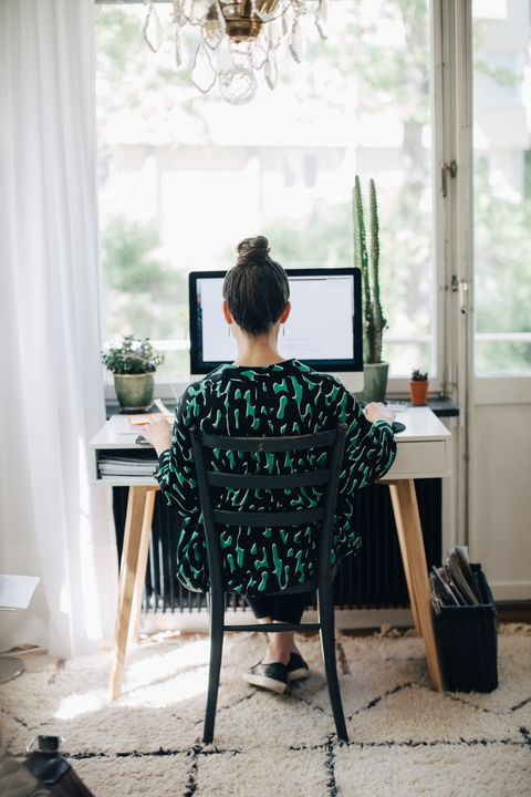 Rear view of businesswoman using computer at desk in home office