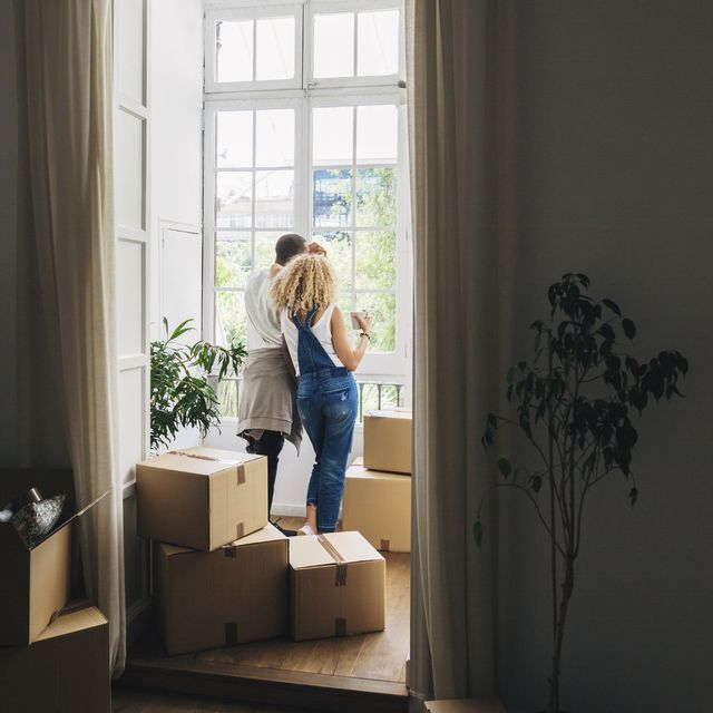 rear view of couple looking through window while standing in new home