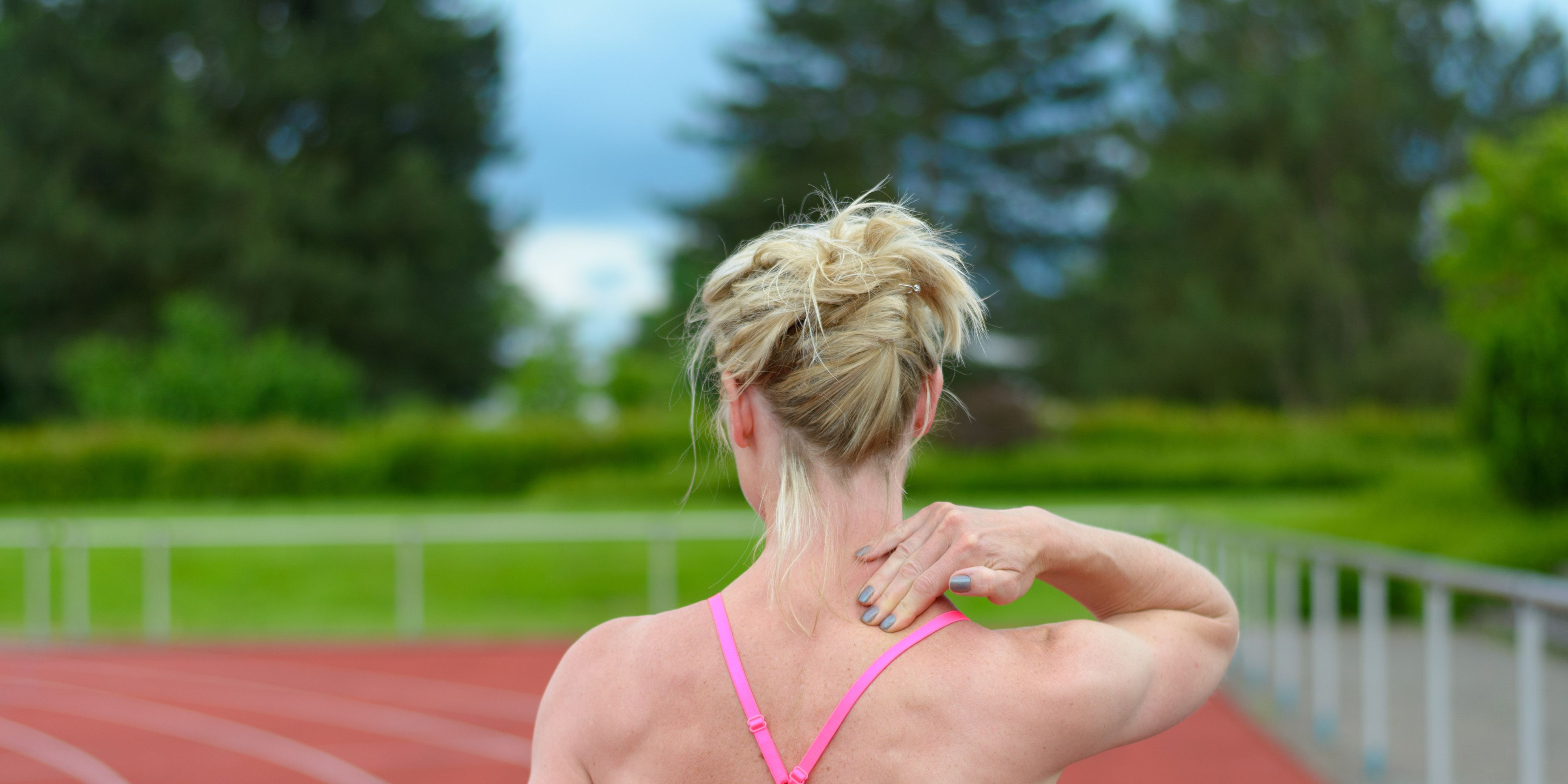Rear View Of Female Athlete Standing With Shoulder Pain On Running Track