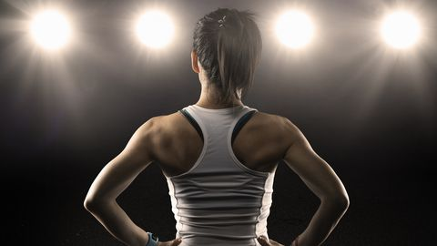 rear view of female athlete wearing sports bra standing with hands