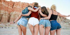 Rear view of four women wearing denim shorts