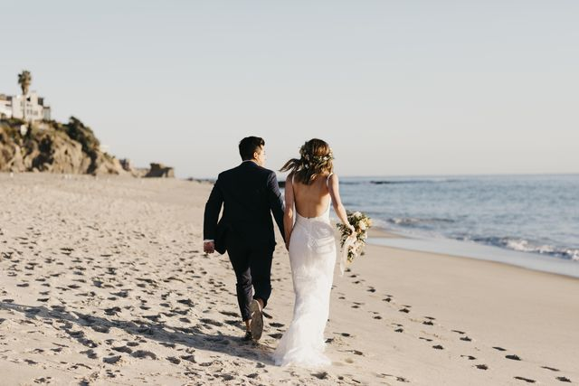 rear view of happy bridal couple running at the beach