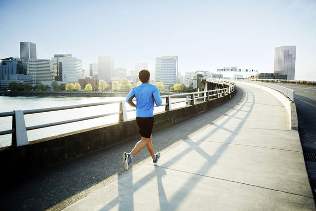 rear view of male athlete running on bridge against clear sky