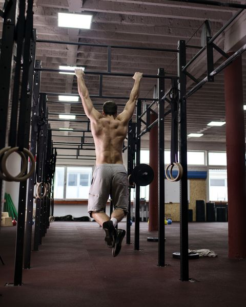 Rear view of man doing chin-ups in gym