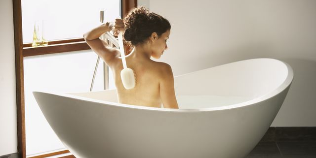 rear view of woman bathing in tub