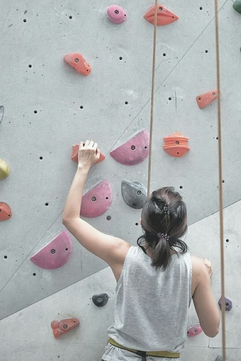 Rear View Of Woman Climbing On Wall