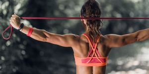 Rear View Of Woman Exercising With Resistance Band