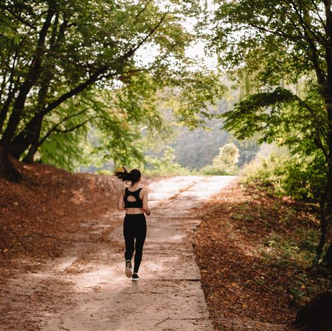 Rear view of woman jogging at park on sunny day