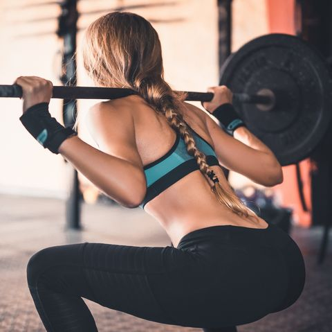 rear view of woman lifting weights in gym