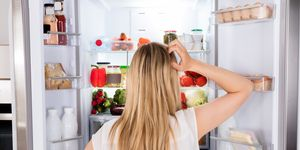 Woman appearing very confused whilst looking at the fridge