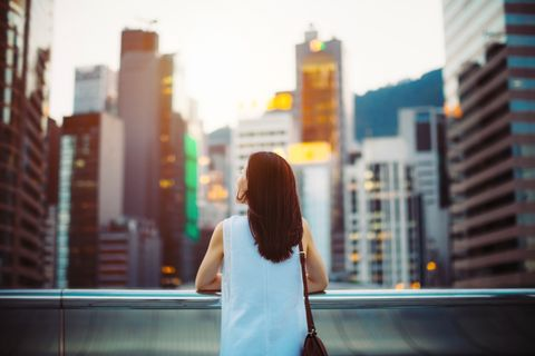 Rear view of woman looking up to sky with smile on a fresh bright morning in city