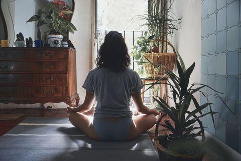 Mujer meditando de espaldas mientras esta en casa