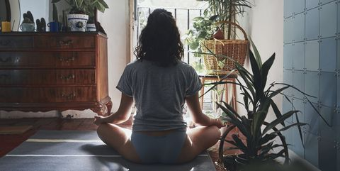 Rear View Of Woman Meditating While Sitting At Home