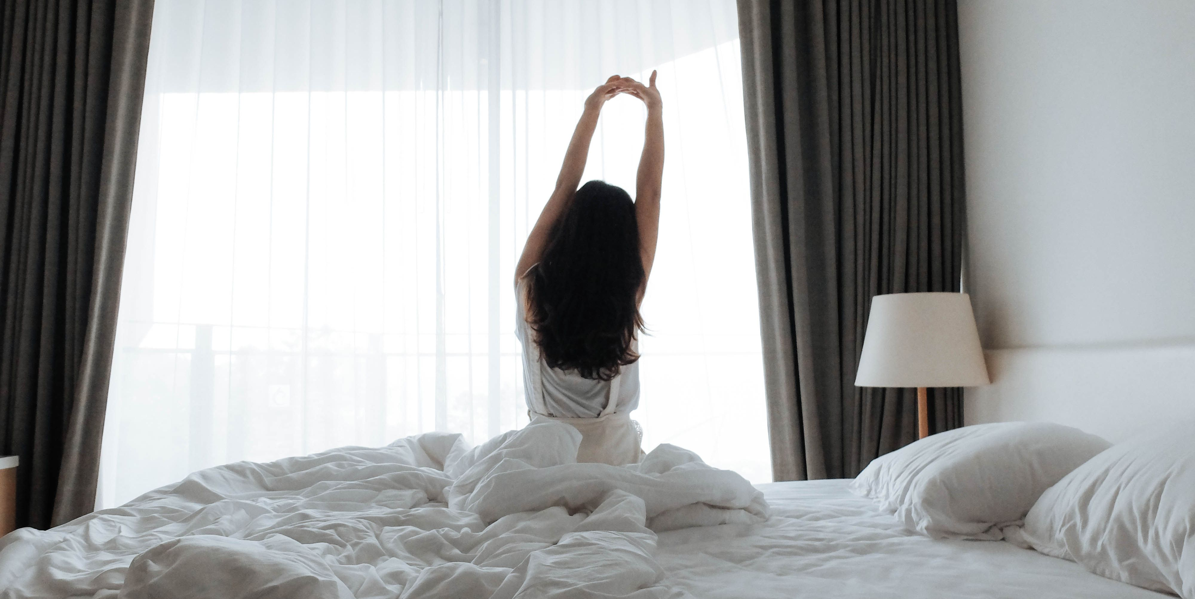 Rear View Of Woman Relaxing On Bed At Home
