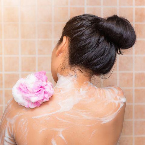 Rear View Of Woman Taking Bath At Bathroom
