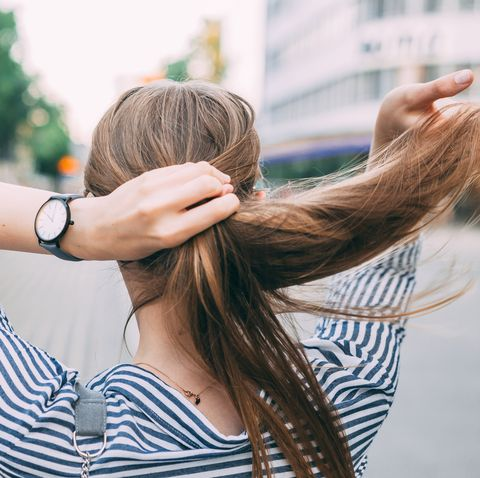 rear view of woman tying hair while standing on road in city