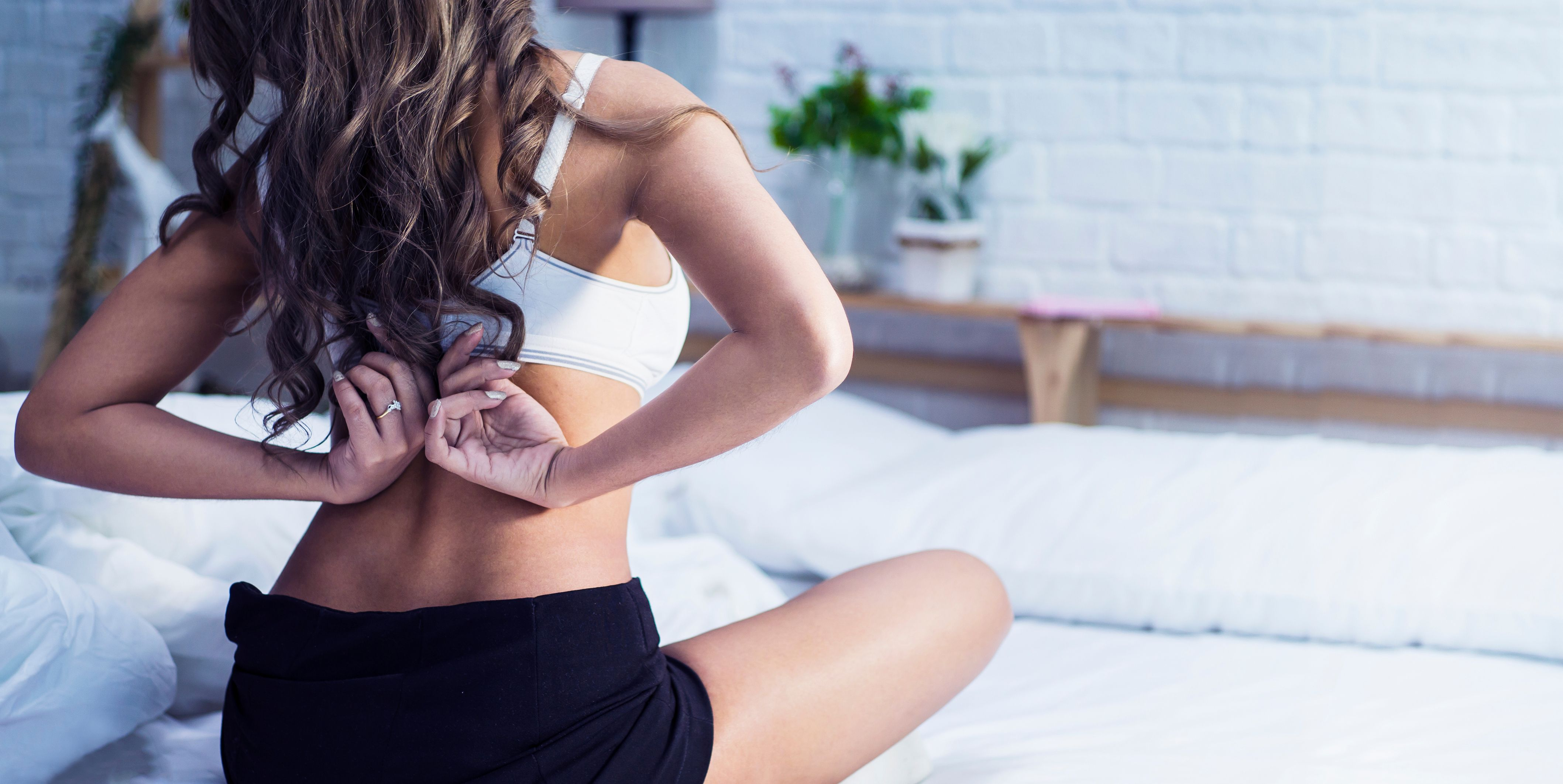 Rear View Of Woman Wearing Bra On Bed At Home