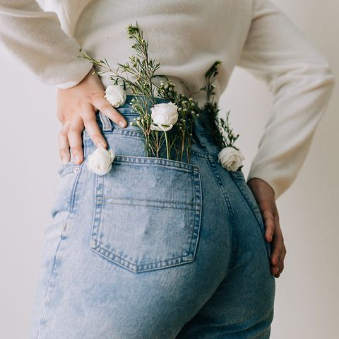 rear view of woman with flowers in pockets