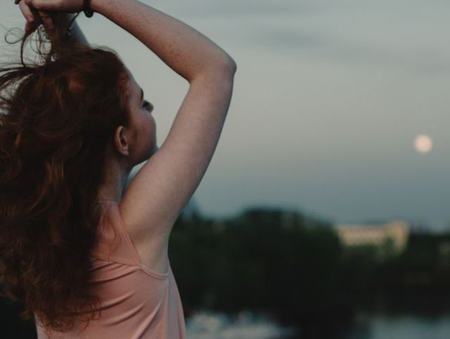 rear view of woman with raised arms standing on bridge at dusk