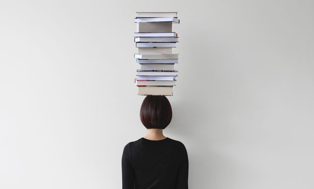 rear view of woman with stack of books on her head