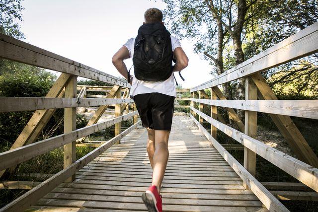 rear view of young male runner running across rural footbridge
