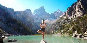 Mujer en postura de yoga frente a un lago.