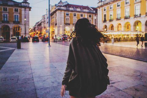 rear view woman walking in the night,Lisbon,Portugal