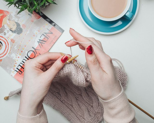 woman knitting with coffee and a new yorker magazine