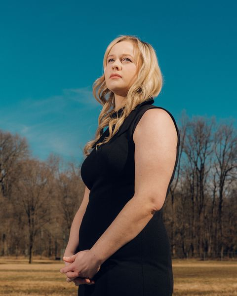 rebekah jones, unsmiling, wearing a black sleeveless dress with a small bow at the collar, standing in front of a clear blue sky and a line of trees with bare branches with her hands clasped