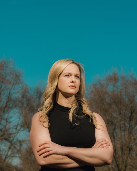 rebekah jones, unsmiling, wearing a black sleeveless dress with a small bow at the collar, standing in front of a clear blue sky and a line of trees with bare branches