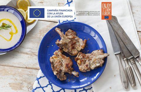 un plato azul con chuletas de cordero hechas a la plancha