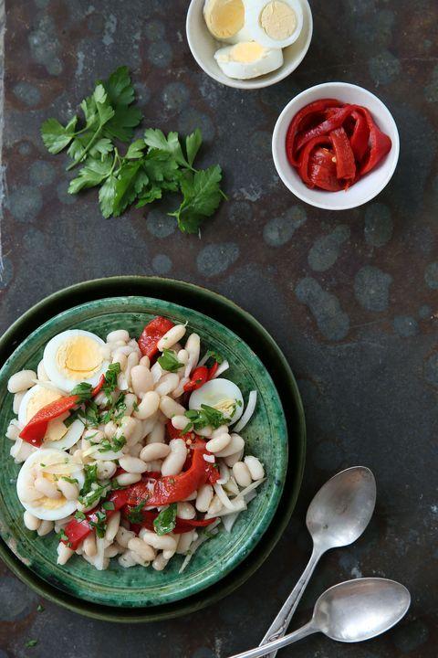 un plato de color verde con alubias frías, huevo cocdo, pimiento rojo, cebolla y perejil