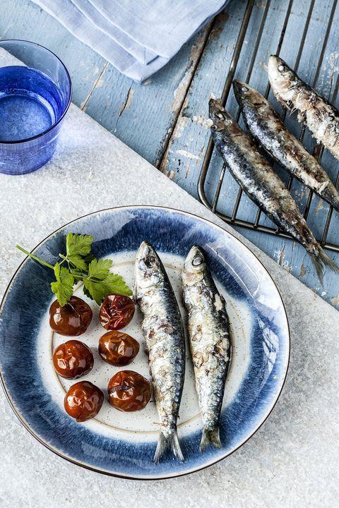 un plato de sardinas asadas con tomates al horno