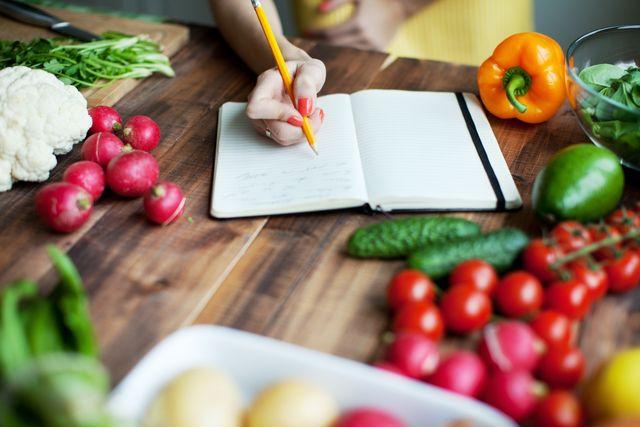 donna scrive ricette su un tavolo con verdure