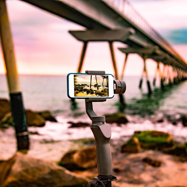 recording with mobile phone using gimbal filming stunning sunrise view of the sea with pier in the catalan coastline