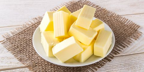 rectangular pieces of fresh yellow butter on a white saucer over a white wooden table dairy sandwich butter natural fat nutrient