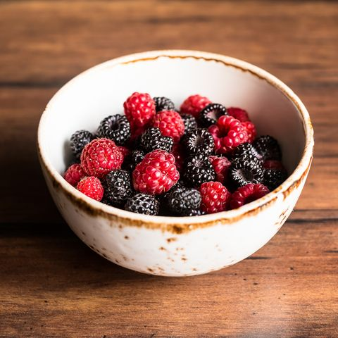 Red and black raspberry in a bowl on a wooden table, selective focus