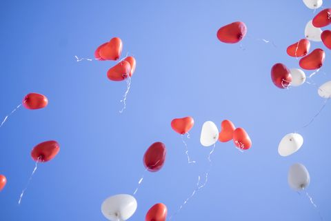 red and white heart shaped balloons flying away in blue sky wedding ceremony