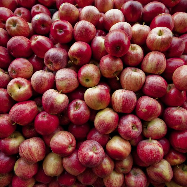 red apples lay in a pile at a fruit stand in maryland, usa