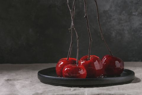 Red caramel apples sweet autumn or Christmas dessert served with branches in black ceramic plate on linen table cloth with grey wall at background. Dark atmospheric mood